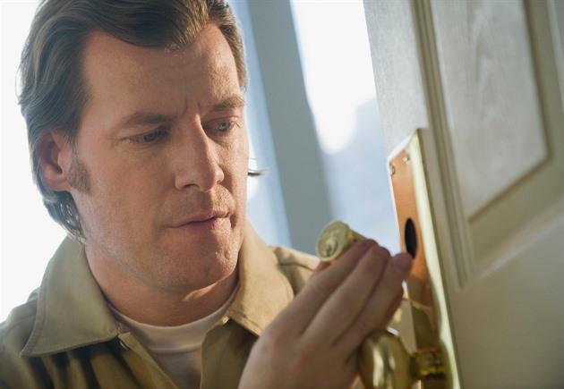 Serrurier qui change la serrure d'une porte d'entrée