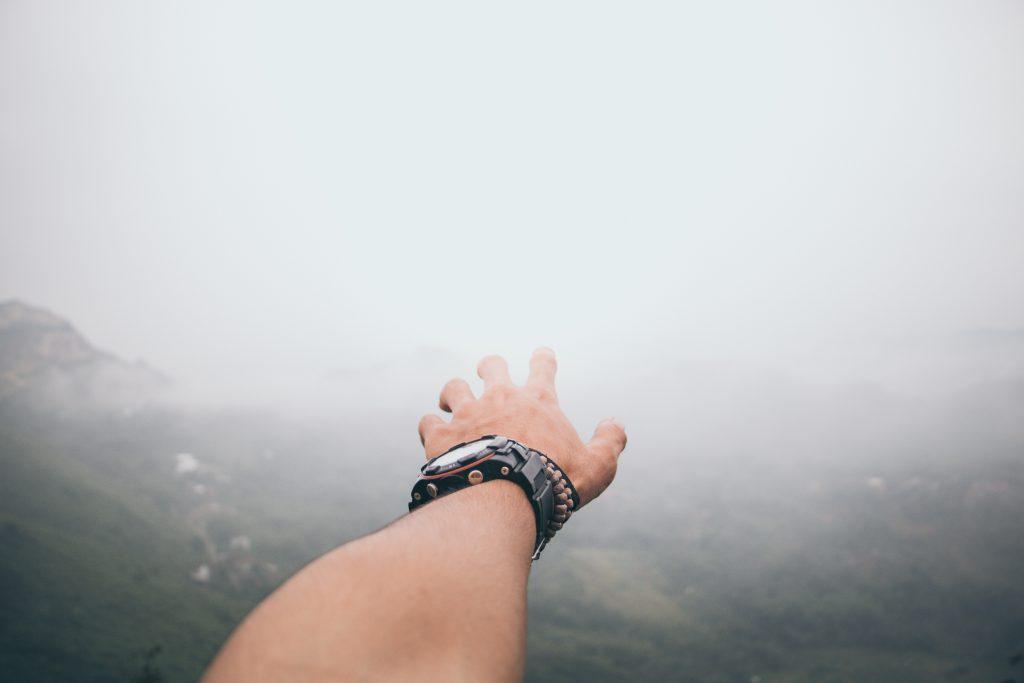 Main d'homme avec montre et bracelets tendus vers le paysage