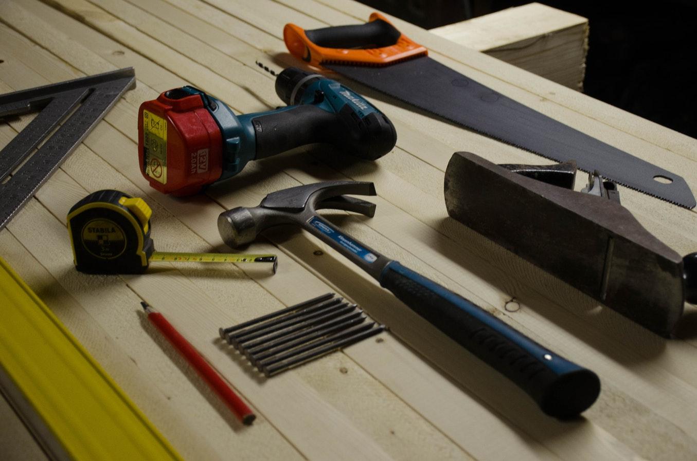 Outils à main et outils électroportatifs posés dans un atelier de bricolage