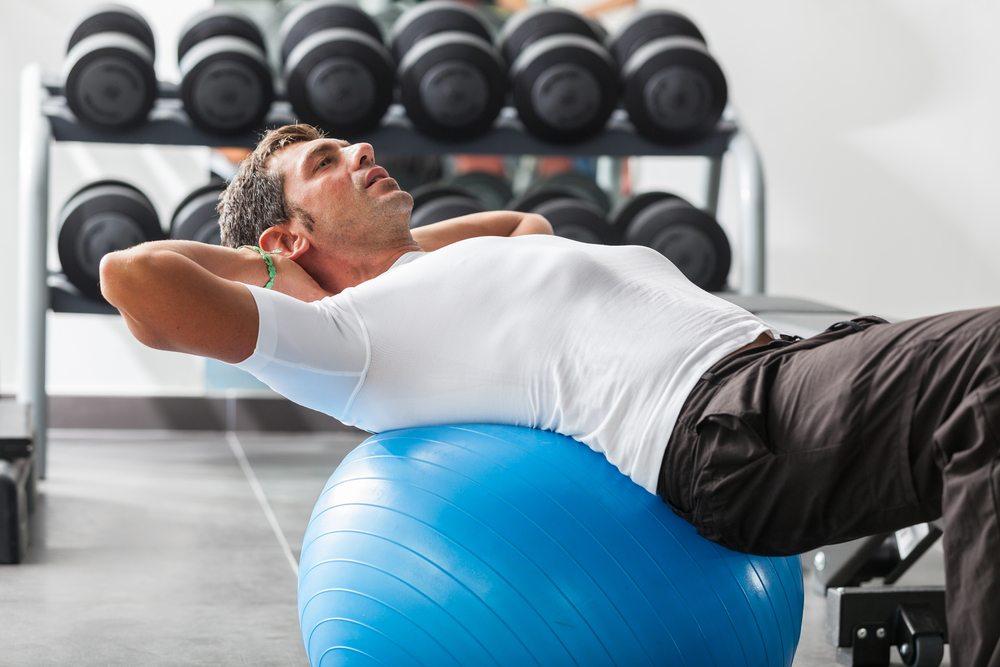 Homme qui réalise un exercice hypopressif sur une balle de sport