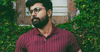 Homme avec une grosse barbe appuyé contre un mur avec du lierre