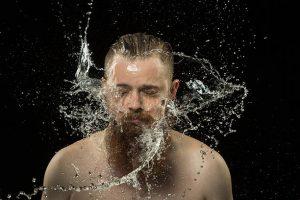 Homme en train de secouer ses cheveux et sa barbe pleins d'eau