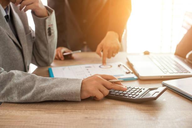 Homme qui se sert d'une calculatrice tandis qu'un autre pointe un document professionnel du doigt
