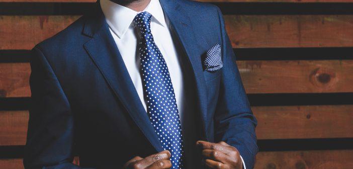 Buste d'un homme en costume bleu avec cravate bleue à pois blancs