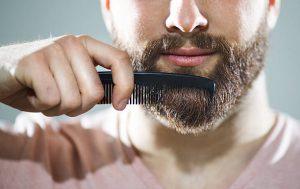 Homme en train de passer un peigne dans sa barbe pour gagner en volume
