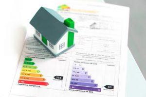 Figurine maison posée sur un bilan de performances énergétiques