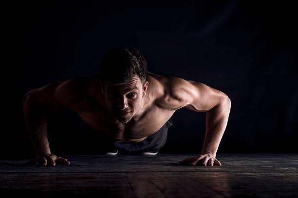 Jeune homme en position de gainage sur fond noir