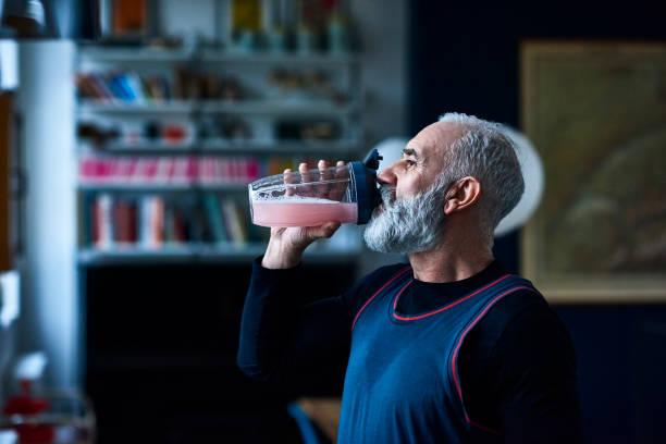 Homme de cinquante ans, de profil, qui boit une boisson énergisante dans un grand verre