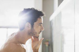 Homme en train d'appliquer un soin sur sa barbe devant le miroir de sa salle de bain