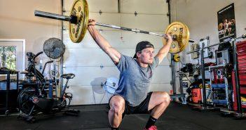 Homme qui fait des squats avec barre de traction dans une salle de sport