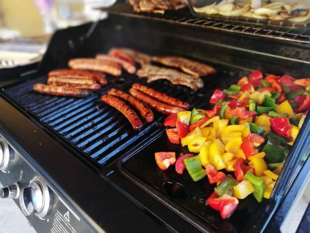 Merguez et poivrons en train de cuire sur un barbecue
