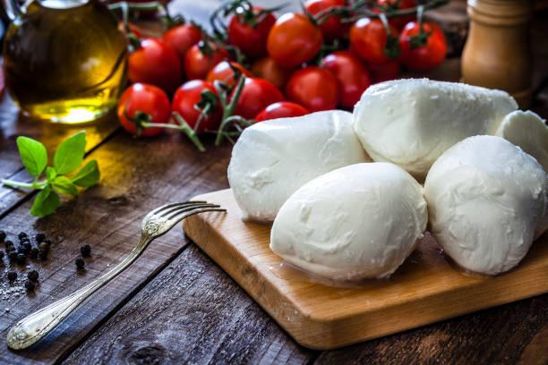 Planche en bois de cuisine avec boules de mozzarella et grappes de tomates dans le fond