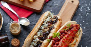 Duo de hot dogs originaux vus de haut sur une planche de cuisine en bois