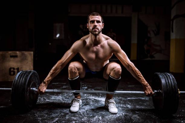 Homme torse-nu qui fait des squats avec une barre chargée de poids