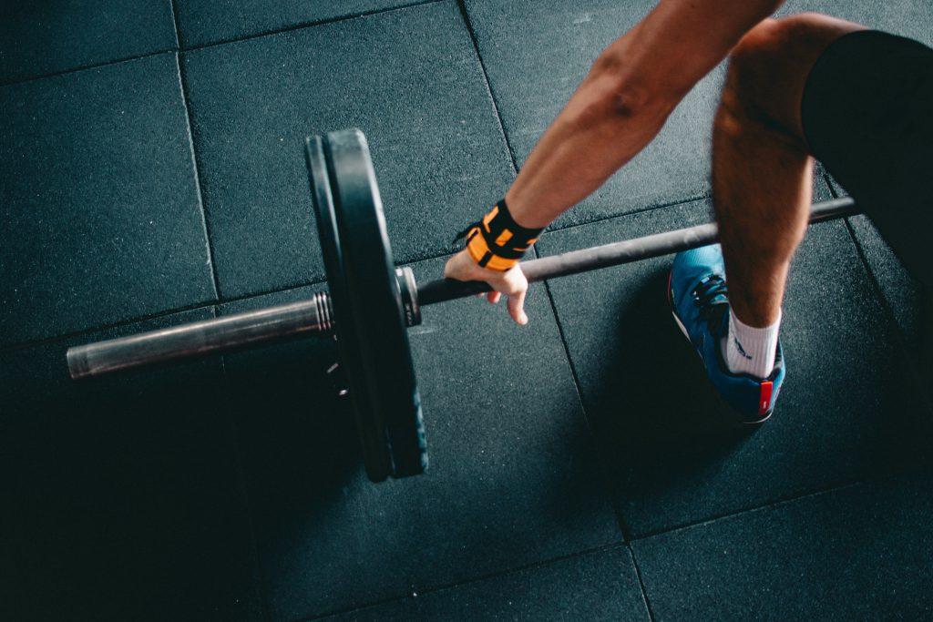 Gros plan sur la barre de traction d'un homme qui fait des squats