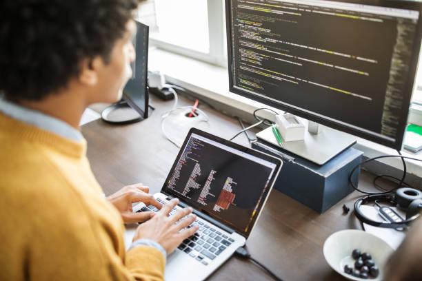 Jeune homme en train de coder des programmes pour un jeu vidéo