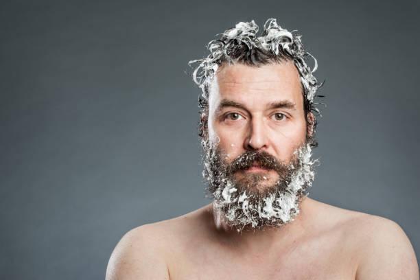 Homme avec shampoing sur les cheveux et la barbe