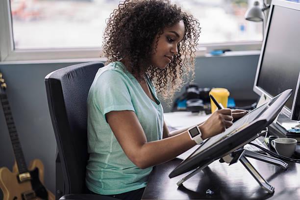 Jeune femme en train de dessiner des personnages de jeu vidéo sur une tablette graphique
