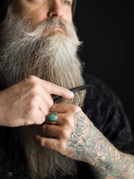 Homme en train de peigner sa barbe blanche