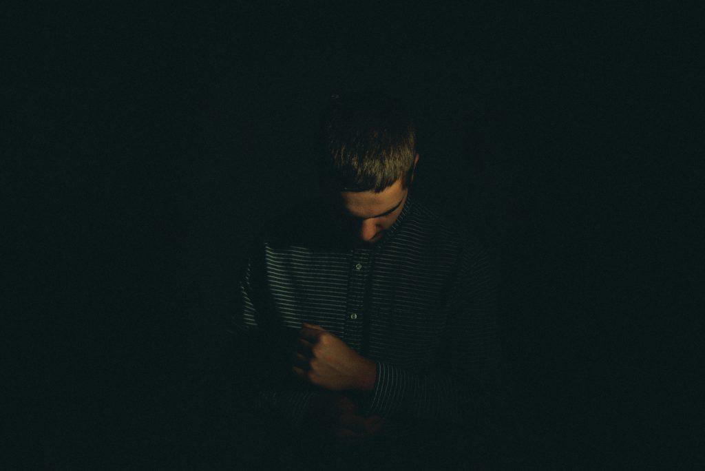 Photographie d'un homme qui pose son poing sur sa poitrine