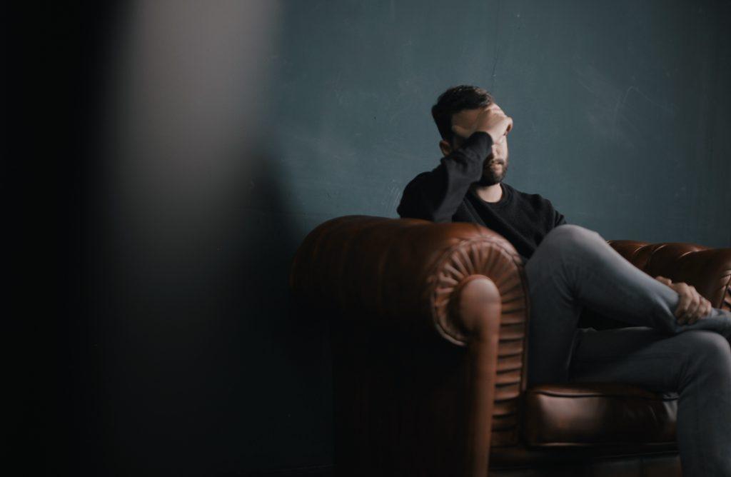 Homme assis sur un canapé qui se tient le visage dans la main