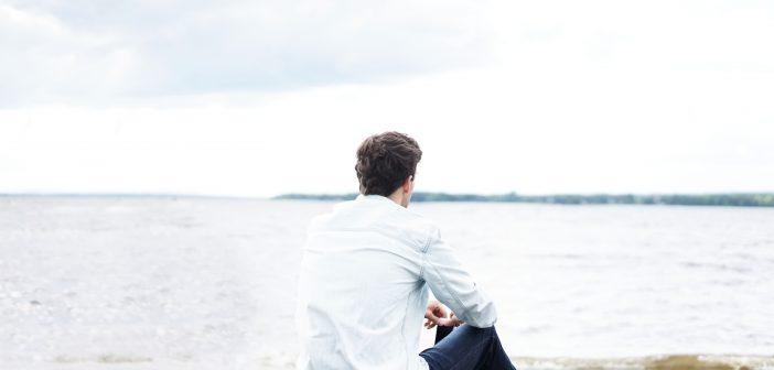 Homme assis sur la plage, qui regarde l'horizon
