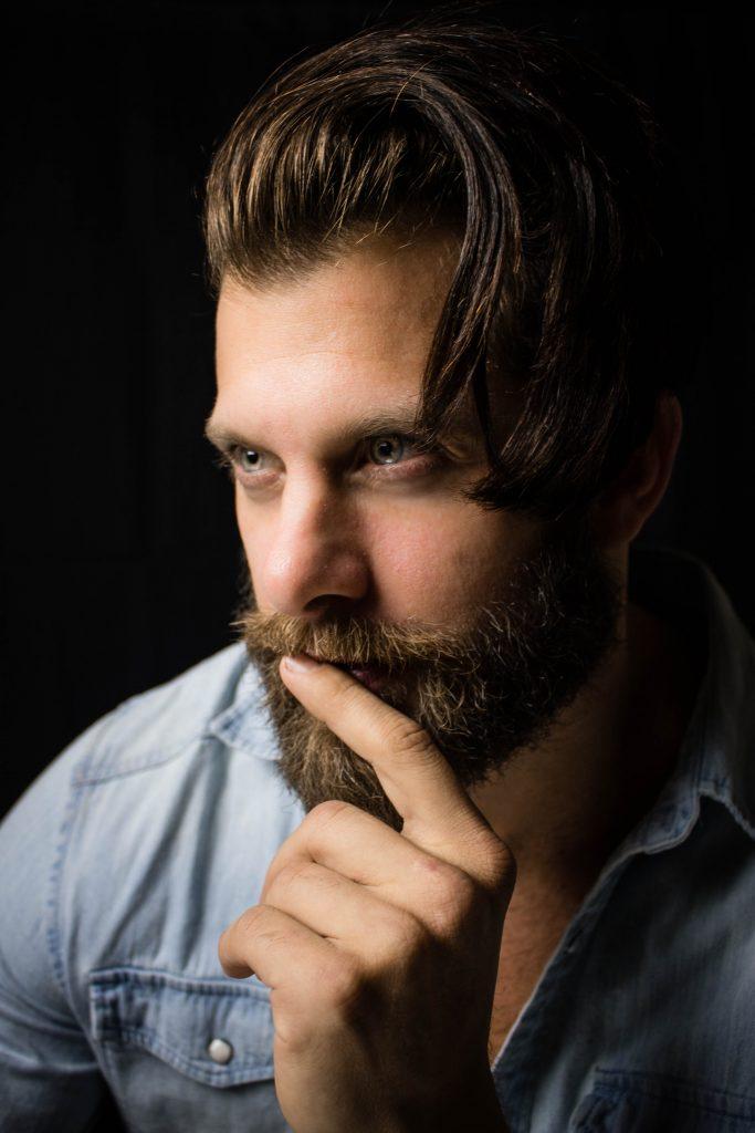 Homme avec une barbe bien fournie qui se tient le menton dans la main