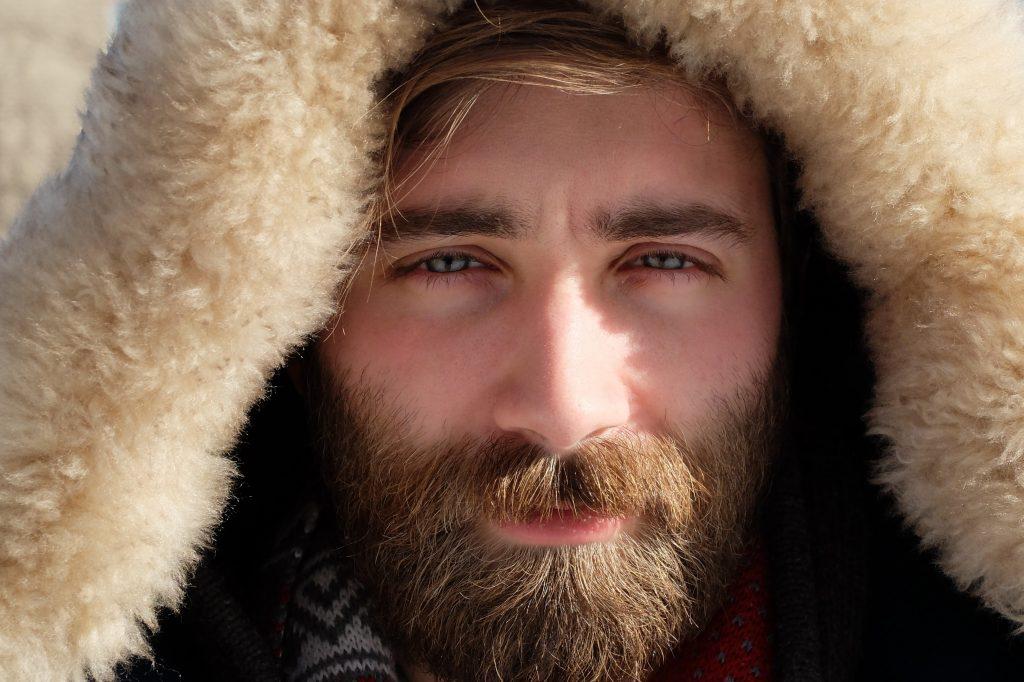 Gros plan sur le visage d'un homme, avec une barbe châtain aux reflets roux et blonds
