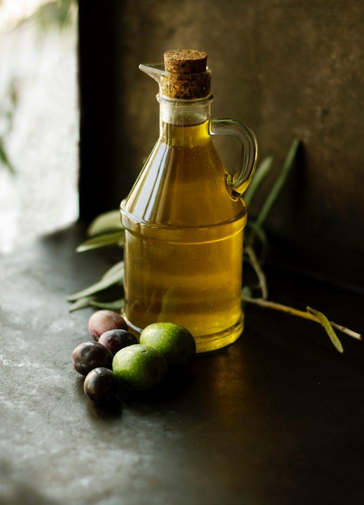 Bouteille d'huile d'olive sur une table, avec une branche d'olivier