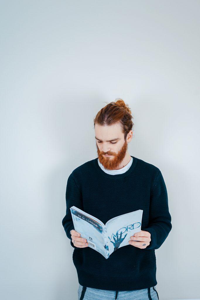 Homme roux avec un man bun qui lit un livre