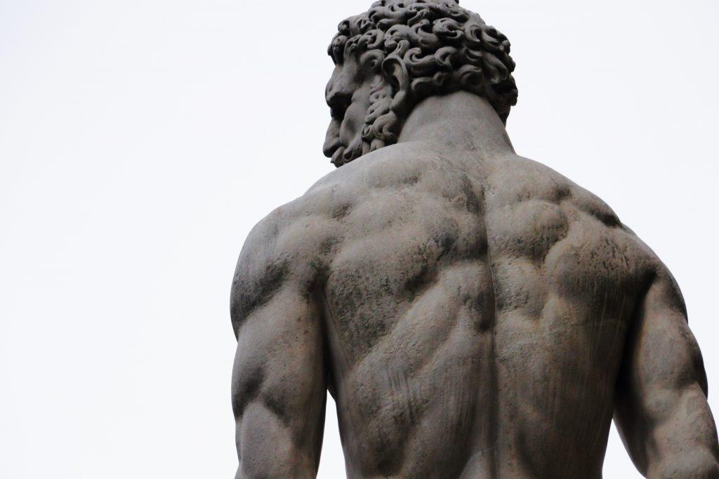 Statue en pierre d'un homme nu au dos musclé