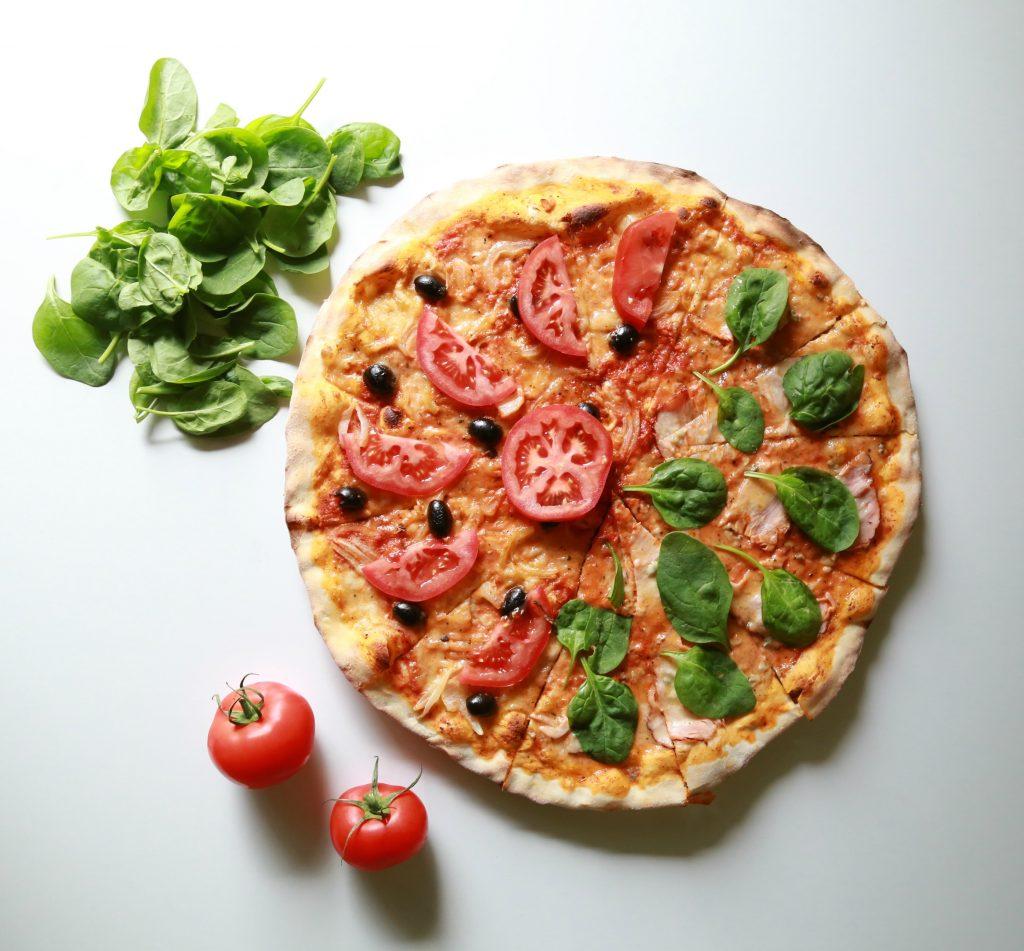 Pizza avec des tomates, des olives et du basilic