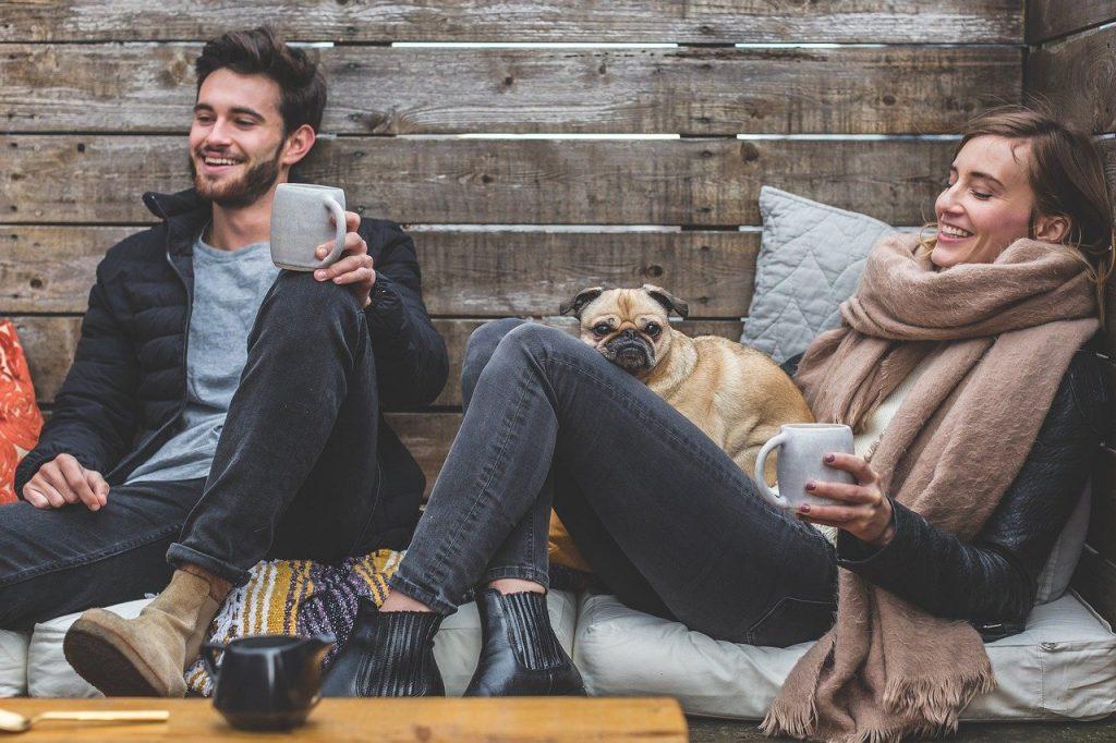 homme et femme en train de boire une boisson chaude accompagnés de leur bouledogue
