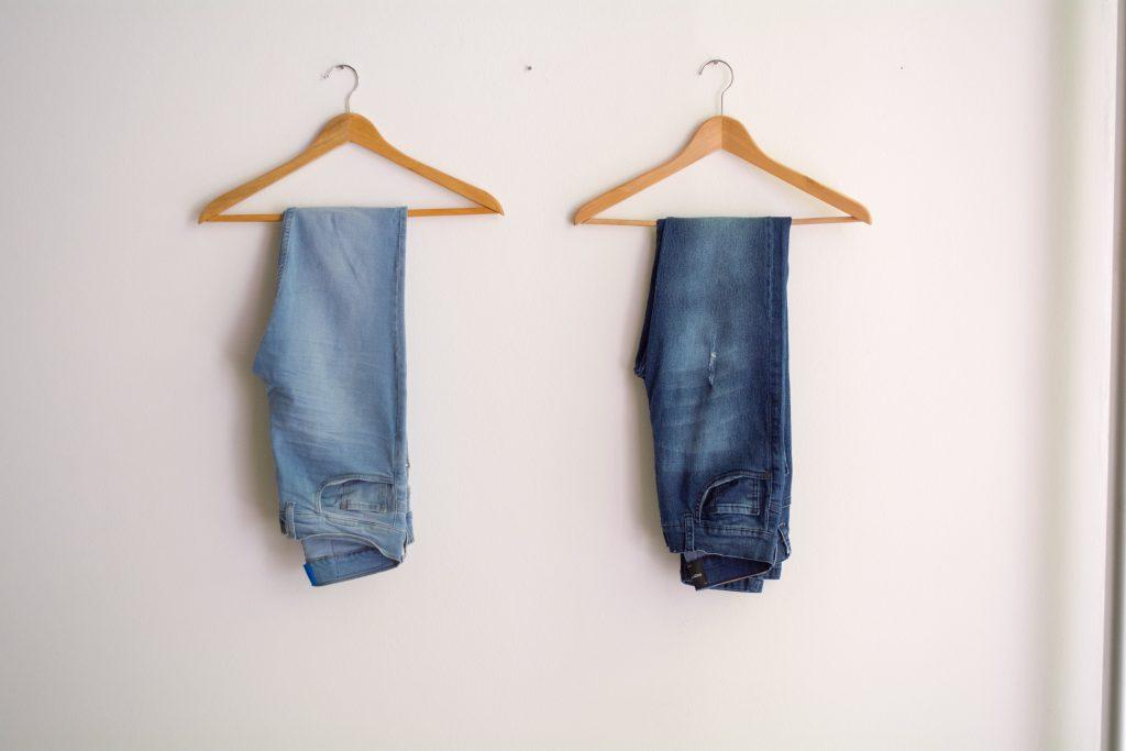 Jeans homme suspendus à des cintres