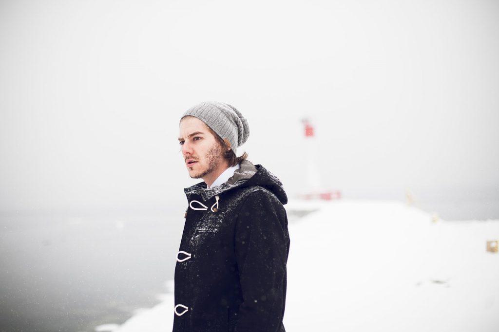 homme qui porte un bonnet et un manteau d'hiver